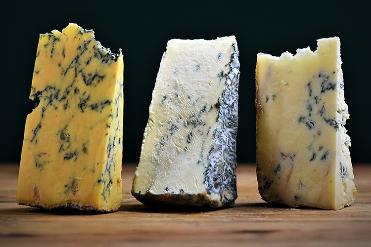 Retouched and enhanced close up of 3 different cheese types laying upright for Cheese Plus