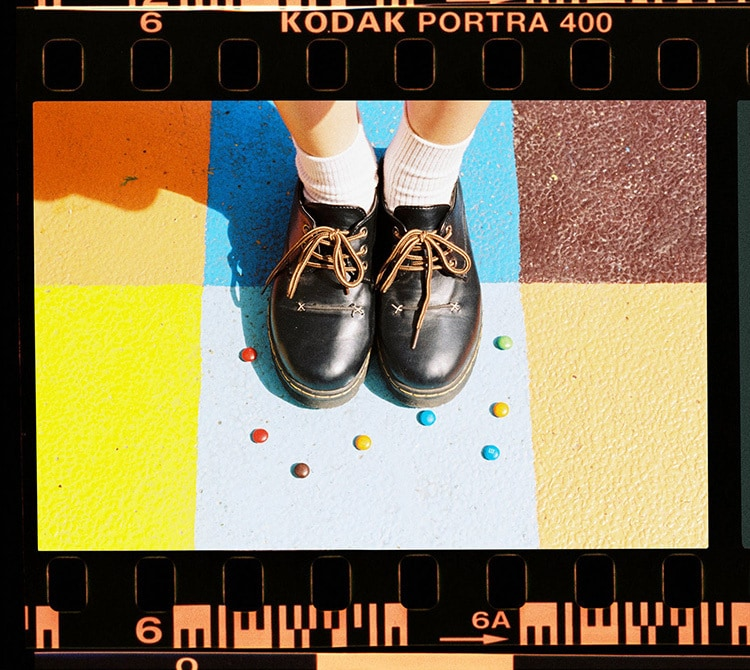 Shoes close together on grided ground with sweets around photography for Kodak Alaris