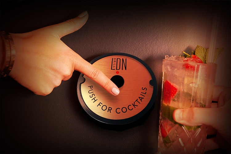 Person hovering Push for Cocktails button for LDN Grill retail design