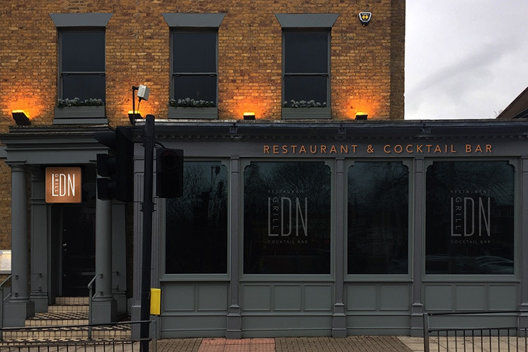 Front of Restaurant with copper signage and window decal with illuminated signage for LDN Grill branding