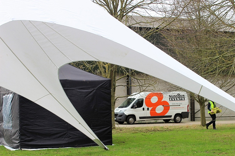 Vans with Number 8 Events branding under a canopy