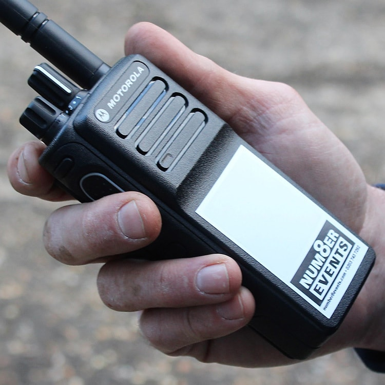 A Person holding a Walkie Talkie with Number 8 Events Branding