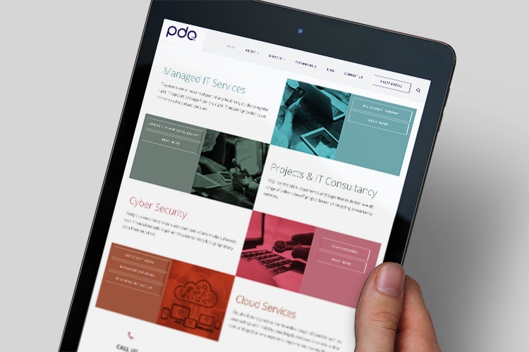 A person holding a tablet viewing the new responsive website design for PDQ