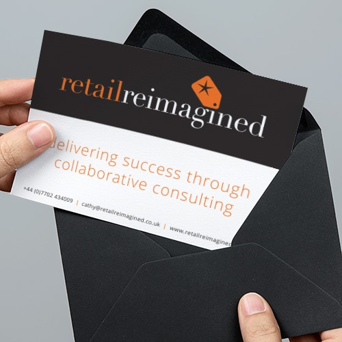 A person pulling out the Retail Reimagined postcard print design