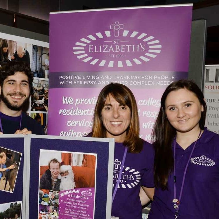 People smiling wearing St Elizabeth's branded T-shirts in front of St Elizabeth's pop up banner design