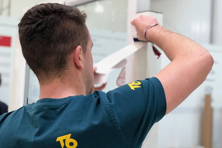 A person wearing T6 branded T-shirt applying tape photography for T6 website