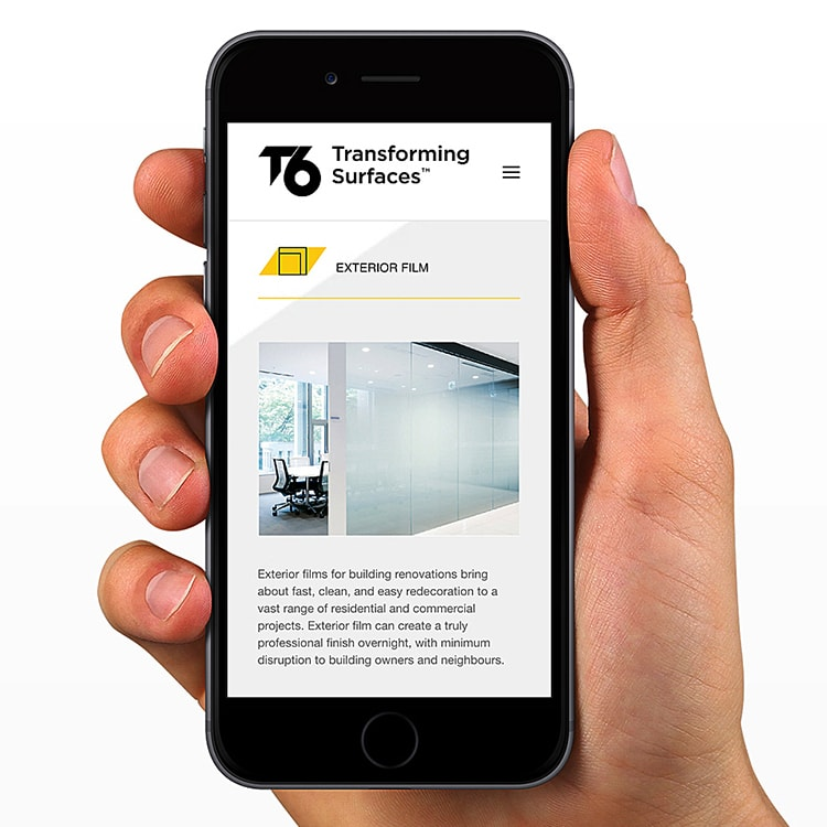 A person holding a mobile phone displaying the responsive T6 website design
