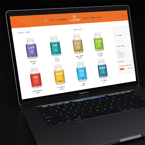 Laptop in a dark room displaying the Vivid Health responsive eCommerce shop page website Thumbnail