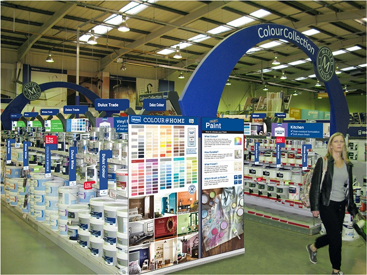 Woman walking past the new Colour collection POS arch design with colour charts for Wickes retail store