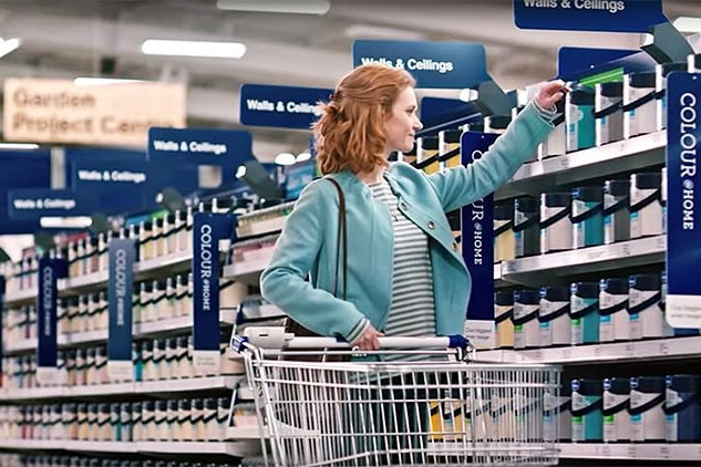A woman holding a trolley and picking a paint bucket photography for Wickes
