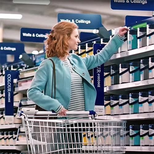 A woman holding a trolley and picking a paint bucket photography for Wickes Thumbnail