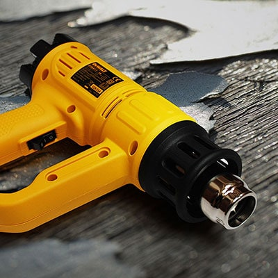 Retouched and enhanced close up shot of a hand heat gun tool with textured background for Tilgear
