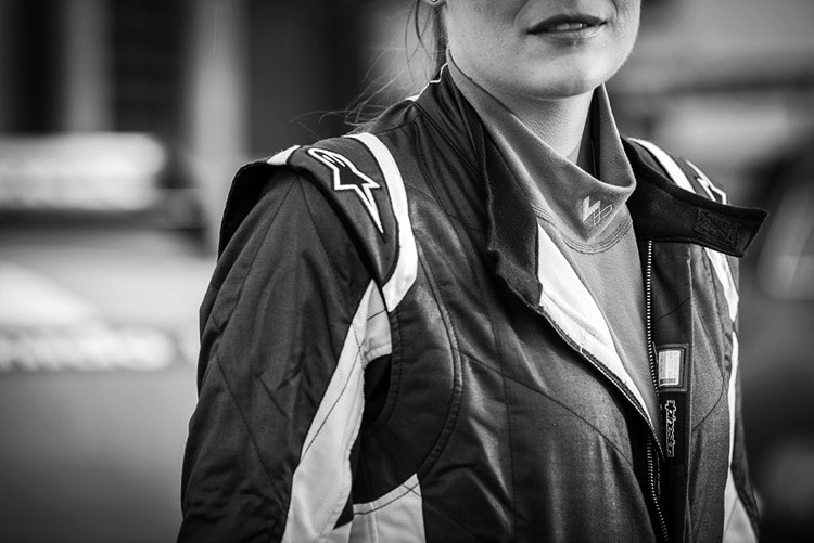 A woman wearing driving equipment and exposing jumper with Walero branding on neck photography for Walero